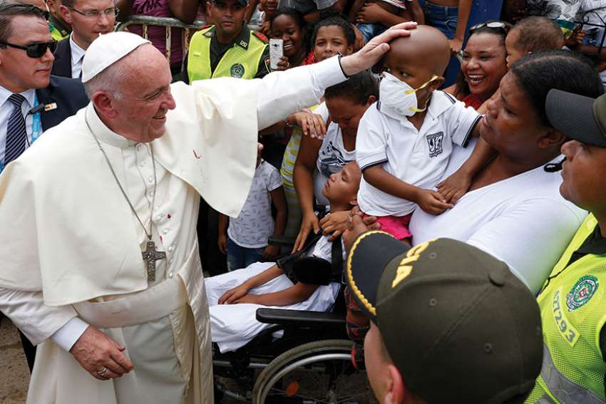 Pope Francis greets a sick child near the Talitha Qum homeless shelter in Cartagena, Colombia, Sept. 10.