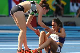 Nikki Hamblin, left, of New Zealand stops running during the race to help fellow competitor Abbey D'Agostino of the U.S. after D'Agostino suffered a cramp during the preliminary women's 5000m Round 1 in Rio de Janeiro on August 16, 2016.