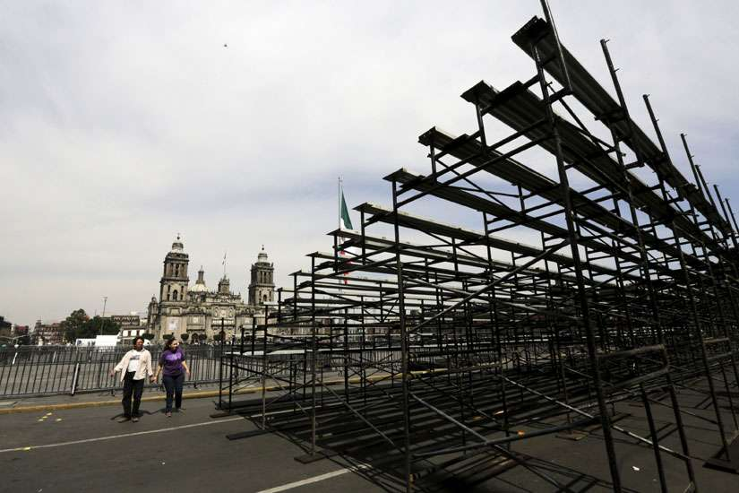 A couple walks the perimeter of Zocalo Square near the Metropolitan Cathedral in Mexico City Feb. 7.