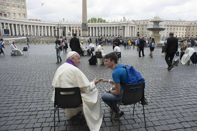 Pope Francis hears confession of a youth April 23 in St. Peter's Square at the Vatican.