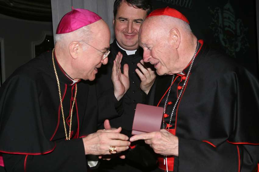 Archbishop Carlo Maria Vigano, then nuncio to the United States, congratulates then-Cardinal Theodore E. McCarrick of Washington at a gala dinner sponsored by the Pontifical Missions Societies in New York in May 2012. The archbishop has since said Cardinal McCarrick already was under sanctions at that time, including being banned from traveling and giving lectures. Oblate Father Andrew Small, center, director of the societies, said Archbishop Vigano never tried to dissuade him from honoring the cardinal at the gala.