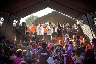 Indonesian President Joko Widodo, center, talks to earthquake victims inside a tent shelter July 30 on the island of Lombok in Indonesia. At least 16 people were killed and hundreds injured July 29 in the magnitude 6.4 earthquake.