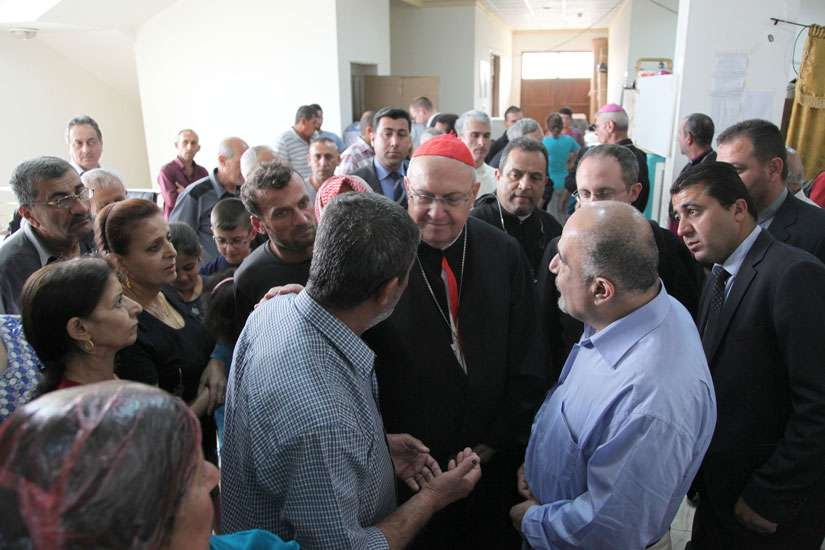 Cardinal Leonardo Sandri, prefect of the Congregation for Eastern Churches, speaks with displaced Iraqis May 4 in Irbil, Iraq.