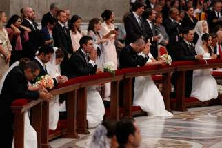 Newly married couples kneel as Pope Francis celebrates the marriage rite for 20 couples during a Mass in St. Peter's Basilica at the Vatican Sept. 14.