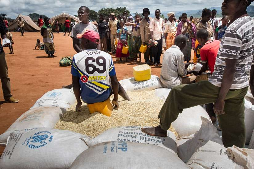 Refugees wait for food rations from the United Nations in early February at a camp in Mwanza, Malawi. In Malawi, where 40 percent of the population needs food aid, the country's bishops have called for international help to avert a crisis.