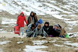 A group of migrants from Syria, Iraq and Afghanistan, on their way to seek asylum in Germany or Austria, walk along the frozen route from the border between Serbia and Macedonia to a temporary camp for migrants. The Archdiocese of Toronto has applied to sponsor another 4,000 refugees this year.