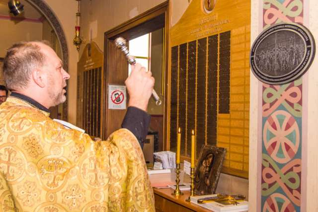 Fr. Jaroslaw Buciora, a Ukrainian priest, blesses one of the 100 identical aluminum plaques which were unveiled at various locations on Aug. 22.