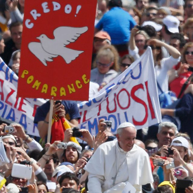 A sign with a dove symbolizing the Holy Spirit is seen as Pope Francis greets the crowd after celebrating a Mass at which he confirmed 44 people in St. Peter's Square at the Vatican April 28. Those confirmed included two young people from the United Stat es and two from Ireland.