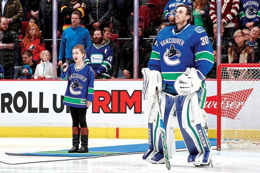 Elizabeth Irving sings the Canadian anthem next to Vancouver Canuck netminder Ryan Miller before a game in 2016.