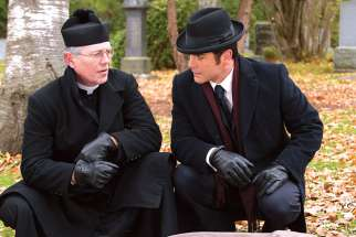 Fr. Keegan (guest star Peter Outerbridge), top left, and Murdoch (Yannick Bisson) discuss the murder scene beside the victim's body in an episode of Murdoch Mysteries. The Fr. Keegan character is based on a priest that Murdoch author Maureen Jennings encountered during her years at Windsor's Assumption University.