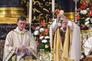 Cardinal Rainer Maria Woelki of Cologne, Germany, and Cardinal Reinhard Marx of Munich elevate the Eucharist during Mass in the cathedral in Fulda, Germany, Sept. 23, 2014.