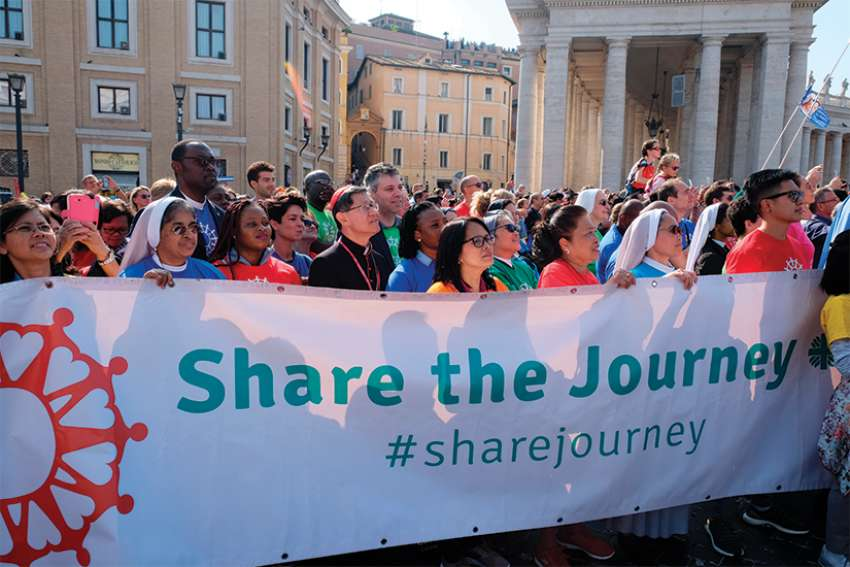 "Cardinal Luis Antonio Tagle of Manila, Philippines, and other participants in the ""Share the Journey"" walk arrive near the Vatican Oct. 21. The campaign and 1.5-mile walk were organized by Caritas Internationalis to call attention to the plight of migrants and refugees."