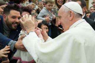 Pope Francis greets a baby during an audience with Italian nurses in Paul VI hall at the Vatican March 3.