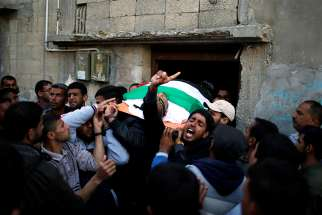 "Mourners carry the body of a Palestinian man, who was killed during clashes at the Israel-Gaza border, during his April 2 funeral in Khan Younis, in the southern Gaza Strip. In his Easter appeal for peace throughout the world, Pope Francis made special mention of the ongoing ""carnage"" in Syria and the recent violence along Israel's border with the Gaza Strip."