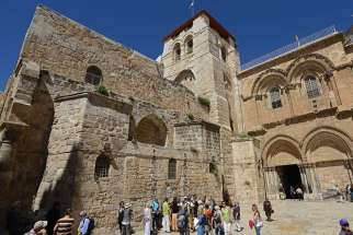 "Pilgrims stand outside the Church of the Holy Sepulchre in Jerusalem's Old City while below a woman prays inside the church. Hundreds of thousands of pilgrims are drawn to the site year round, but never so much as during Holy Week. Biblical scholar Murray Watson said pilgrims become conscious of walking on holy ground and ""being at the literal heart of the Christian Gospel."""