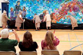 "Sisters of Charity (also known as the Grey Nuns) participate in the unveiling of ""The Humble Seamstress,"" a mural at Edmonton's St. Alphonse Academy honouring Sr. Marie Alphonse, the province's first educator."