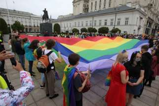Demonstrators hold a giant rainbow flag during a protest against hatred toward LGBT people in Warsaw, Poland, Aug. 30, 2020.