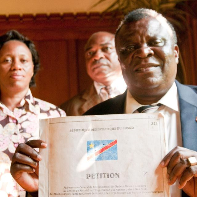 United Methodist Bishop Ntambo Nkulu Ntanda displays one volume of the million-plus name petition to the United Nations demanding meaningful peacekeeping and serious consequences for the Rwandan government for supporting militias in the eastern Democratic Republic of Congo. Behind him are Mme. Emma Zanao Selenani and Prof. Raymond Mande Mutombo.