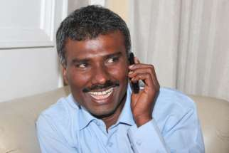 Jesuit Father Alexis Prem Kumar, who was kidnapped in Afghanistan and was held for more than eight months, speaks on a cell phone on his arrival in New Delhi Feb. 22.