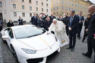Pope Francis autographs a Lamborghini Huracan coupe presented by representatives of the Italian automaker at the Vatican in this 2017 file photo. The custom-built 2018 Lamborghini is back on the block, this time with an online fundraising platform, not at an elite European auction house.