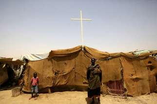 People from South Sudan stand near a tent used as a church at a railway station camp, where they have spent the last four years, in Khartoum on May 11, 2014.