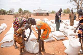 Young women help each other carry sacks of sorghum and beans March 17 after receiving them at a distribution center in Yirol, South Sudan. July 9 marks the sixth anniversary of worldÕs youngest country as it is