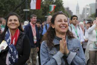 A woman reacts to Pope Francis' final words during the closing Mass of the World Meeting of Families on the Benjamin Franklin Parkway in Philadelphia Sept. 27.