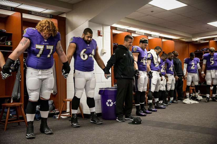 Baltimore Ravens head coach John Harbaugh prays with players after they defeated the Cleveland Browns 20-10 in 2014 at M&T Bank Stadium in Baltimore. Harbaugh says he has relied on his Catholic faith to guide him and his players as they have faced various challenges during the past year.