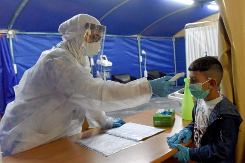 A nurse wears a protective suit while taking the temperature of a Palestinian boy in a special tent for pediatric and maternity COVID-19 patients at St. Joseph's Hospital in East Jerusalem April 16, 2020.