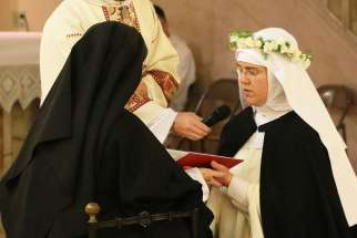 Sister Marie Dominic, right, professes her first vows as a cloistered nun May 28 at Corpus Christi Monastery in Menlo Park, Calif. Sister Marie Dominic was an attorney and an evangelical Christian in Anchorage, Alaska, who joined the Catholic Church during her last months of law school.