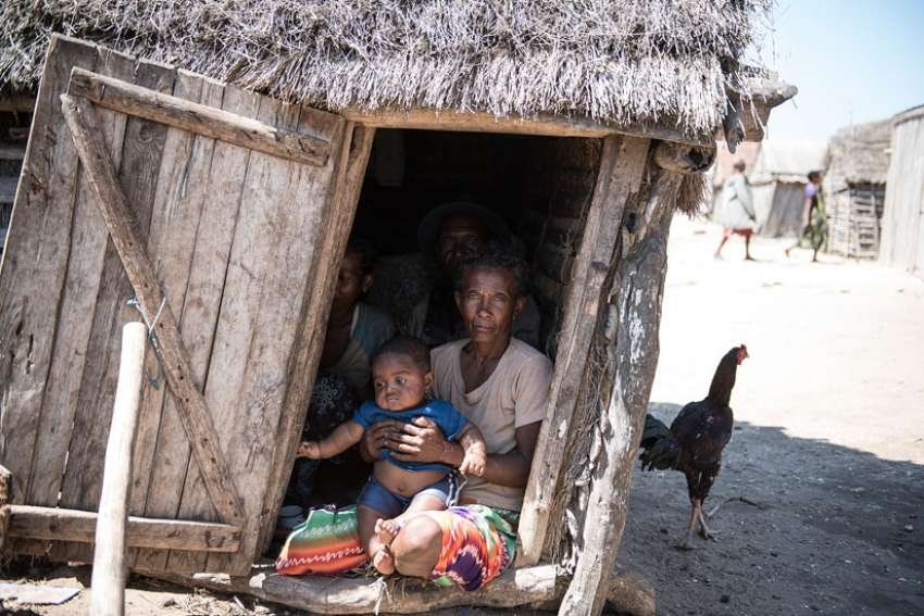 A family sits inside their hut in Ambovombe, Madagascar, Sept. 22, 2015. Hunger levels are now so severe in drought-ridden southern Madagascar that many people in remote villages have eaten almost nothing but cactus fruit for up to four years, said a Catholic Relief Services official.