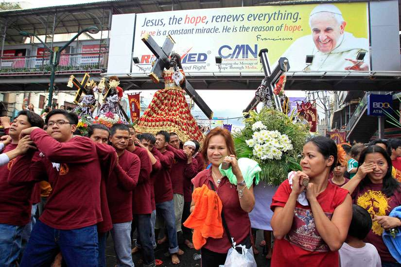 Men and women carrying replica statues of the Black Nazarene walk under a banner of Pope Francis during a procession in Manila, Philippines, Jan. 7. Millions of devotees are expected to attend the annual procession of the Black Nazarene Jan. 9. The Black Nazarene, a life-size wooden statue of Christ carved in Mexico and brought to the Philippines in the 17th century, is believed to have healing powers in the predominantly Catholic country.