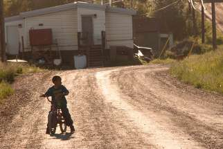 A young boy rides his bike around his neighbourhood on an Indigenous reserve.