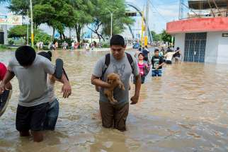 People cross a street flooded by the Piura River March 27 in Peru.