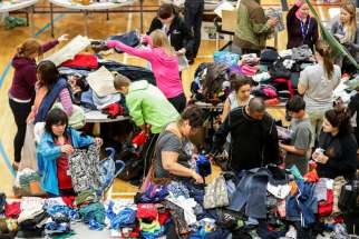 Evacuees from the Fort McMurray wildfires look through donated goods and clothing May 5 at the Bold Center in Lac la Biche, Alberta. Pope Francis has added his name to the list of people offering condolences to those affected by the massive forest fire that has led to the evacuation of Fort McMurray.