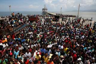 People in Jeremie, Haiti, wait for relief to be unloaded from a Dutch navy ship Oct. 16.