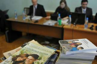 Stacks of booklets distributed by Alexander Kalistratov, left, the local leader of a Jehovah's Witnesses congregation, are seen during the court session Dec. 16, 2010, in the Siberian town of Gorno-Altaysk.