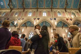 A mother and her toddler attend Mass at Toronto's St. Michael's Cathedral Basilica Sep. 30, 2016.