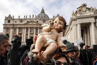 An audience member holds a figurine of baby Jesus as Pope Francis leads his Sunday Angelus prayer in St. Peter's Square at the Vatican Dec. 16.