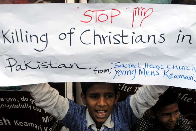 A Pakistani Christian boy holds a banner during a late March protest in Karachi after attacks on churches in Lahore. The U.S. State Department's annual report on the status of religious freedom around the world was released in Washington Oct. 14.