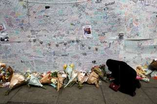 A woman kneels in prayer June 16 beside a message wall near a London apartment building destroyed in a June 14 fire. Church authorities in London confirmed that students from nearby Catholic schools are among the missing from the June 14 fire.