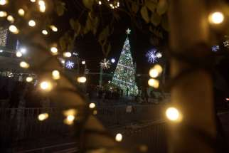 People attend the lighting of the Christmas tree on Manger Square in Bethlehem, West Bank, Dec. 5.