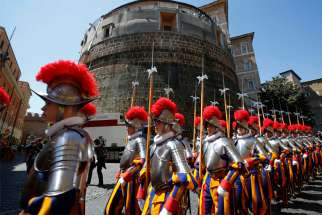 In this 2014 file photo, recruits of the Vatican's Swiss Guard march in front of the tower of the Institute for Works of Religion, often referred to as the Vatican bank.