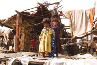 Pakistani children stand outside their makeshift home near Karachi.