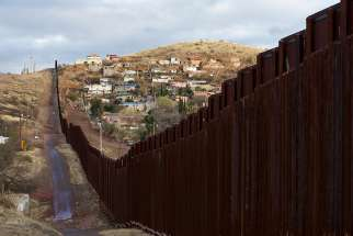 The bollard steel border fence splits the U.S. from Mexico in this view east of central Nogales, Ariz., Feb. 19.