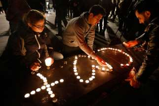 People light candles in the shape of a cross and heart in Republique square in Paris Nov. 14 in memory of victims of terrorist attacks.