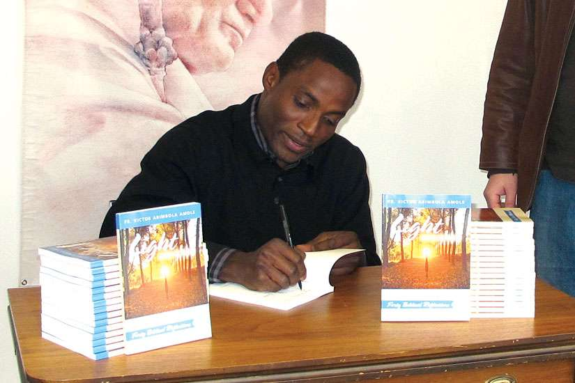 Fr. Victor Amole signs copies of his new book, Light Unto My Path: Forty Biblical Reflections.
