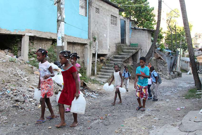 Children in Santo Domingo, Dominican Republic, carry containers for water Sept. 6 as Hurricane Irma races across the Caribbean. The hurricane was scheduled to hit the island later that night.