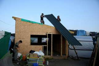 "Men remove the roofing of a makeshift shelter Oct. 25, as part of the dismantlement of the camp called the ""Jungle"" in Calais, France."