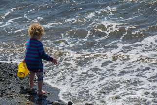 A child walks along the shores of Lake Ontario.